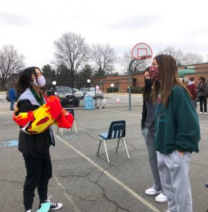 Seniors Christine Duong, Sophia Nguyen, and Kayla Nguyen attend a socially distanced senior event on the school basketball court.